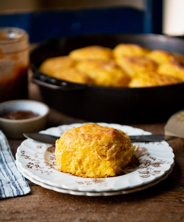 Light and flaky sweet potato biscuits on a small plate on a dinner table