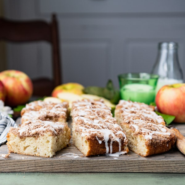 Front shot of apple coffee cake with sour cream on a wooden cutting board