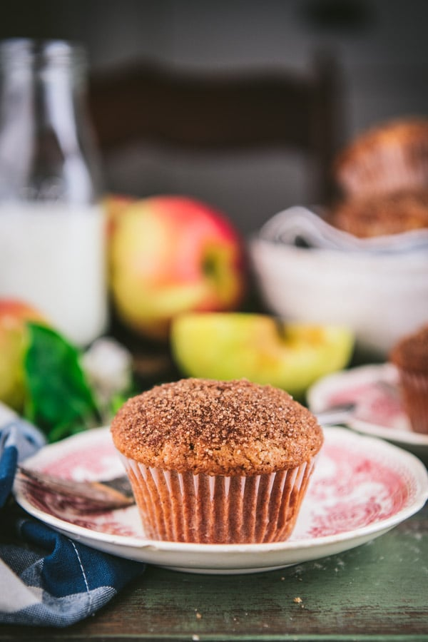 Side shot of apple muffins with cinnamon sugar topping on a wooden table