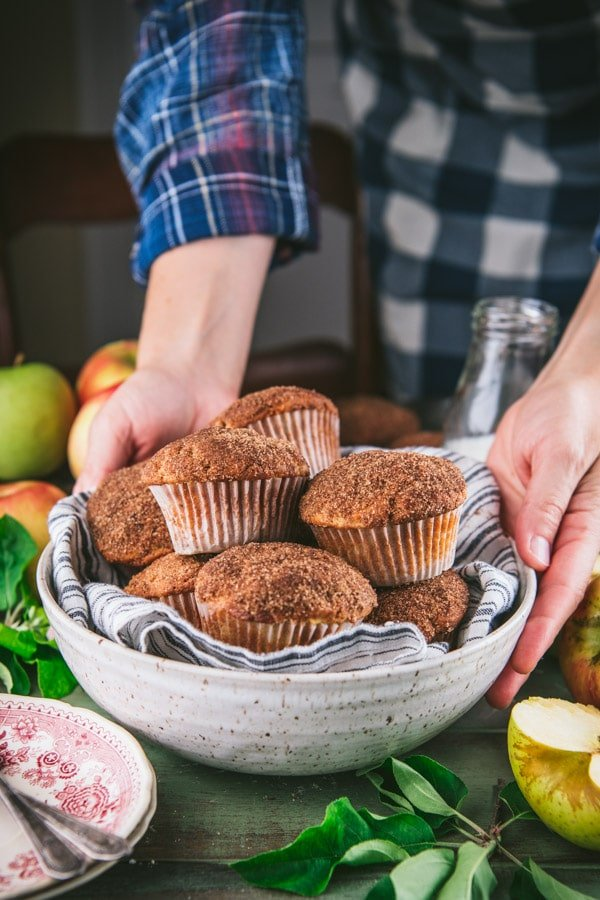 Hands serving a basket of easy apple muffins on a dinner table