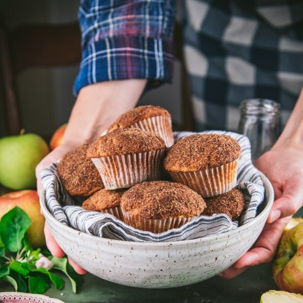 Square shot of arms serving a bowl of apple muffins