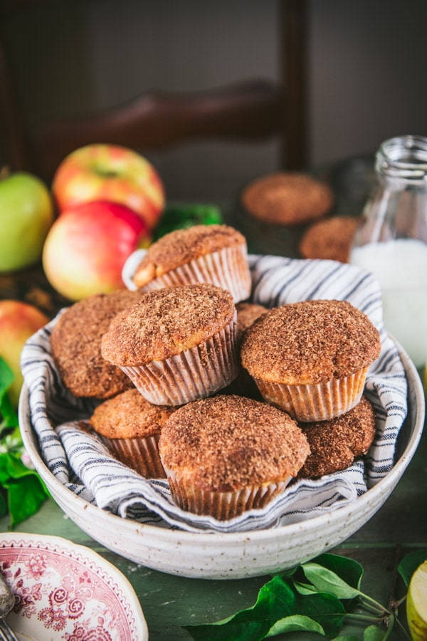 Bowl of apple cinnamon muffins on a table with milk and apples in the background