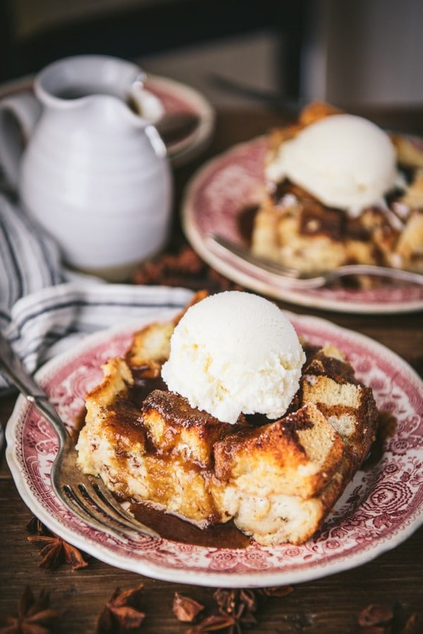 Close up shot of the best bread pudding recipe served with bourbon sauce and vanilla ice cream.
