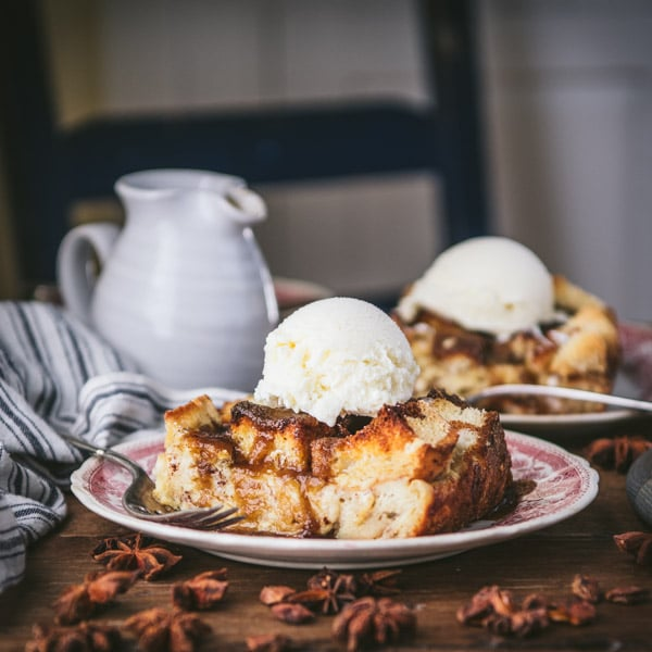 Square image of two plates of bread pudding on a wooden table.