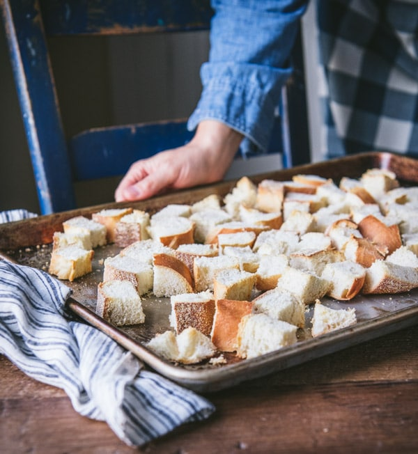 Dry cubed bread on a rimmed baking sheet
