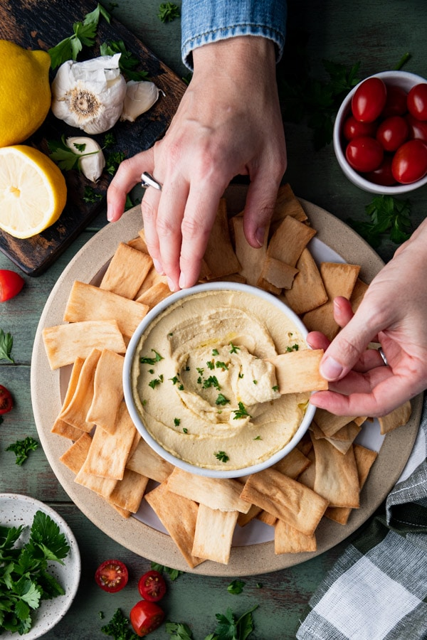 Hands dipping pita in a bowl of the best hummus recipe