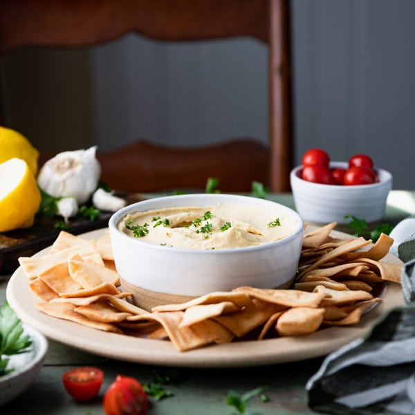 Square image of a bowl of the best hummus recipe with tahini on a table