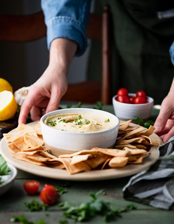 Hands serving a plate of easy hummus and pita chips