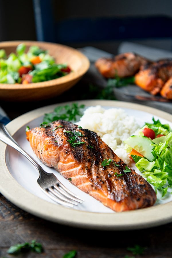 Close up front shot of a grilled salmon fillet on a white plate