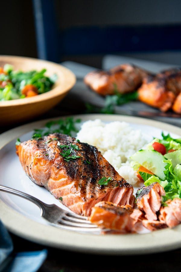 Close up side shot of grilled salmon with skin on a white plate with a salad in the background