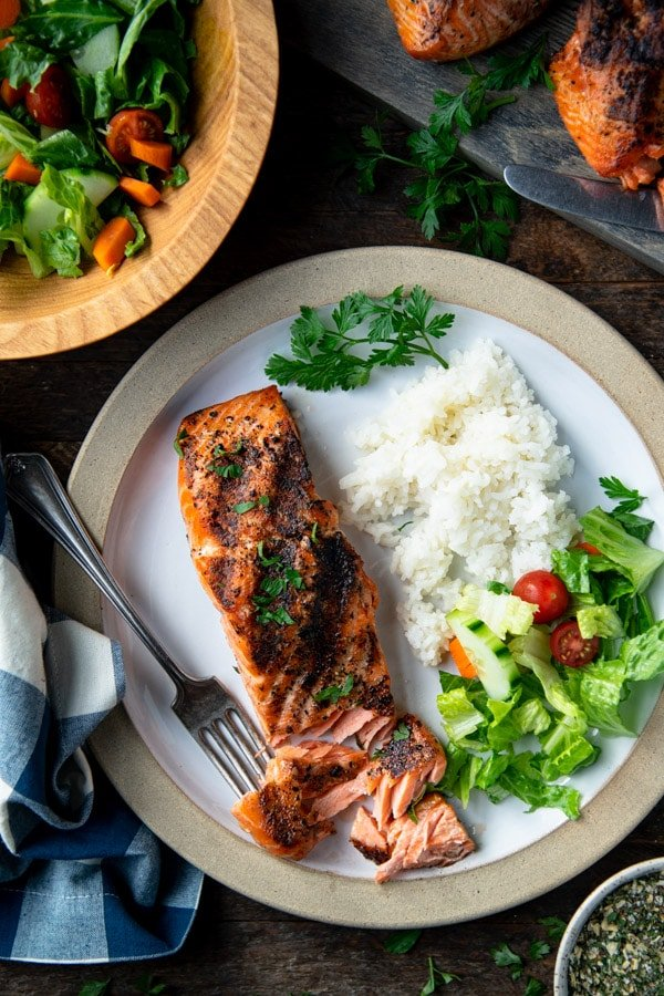 Overhead shot of a piece of grilled salmon on a white plate with rice and salad