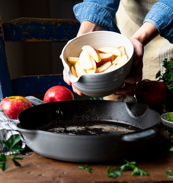 Adding a bowl of sliced apples to a cast iron skillet