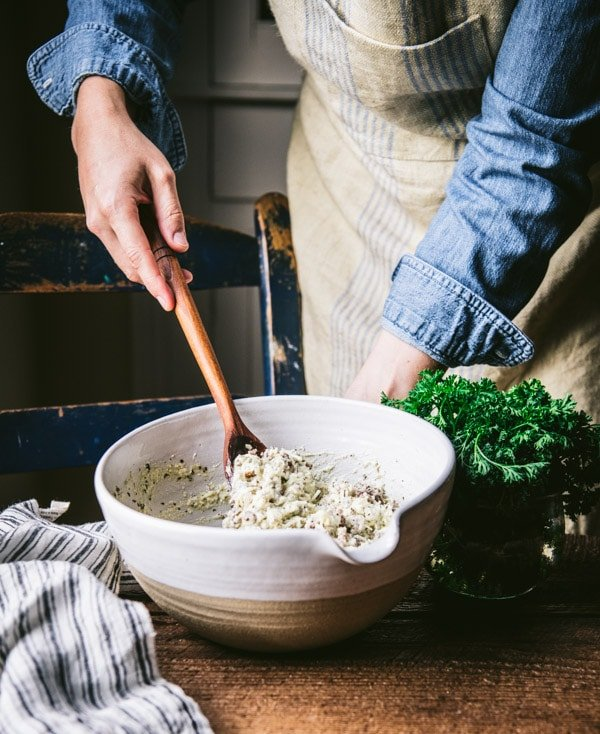 Stirring a ricotta cheese mixture in a white bowl