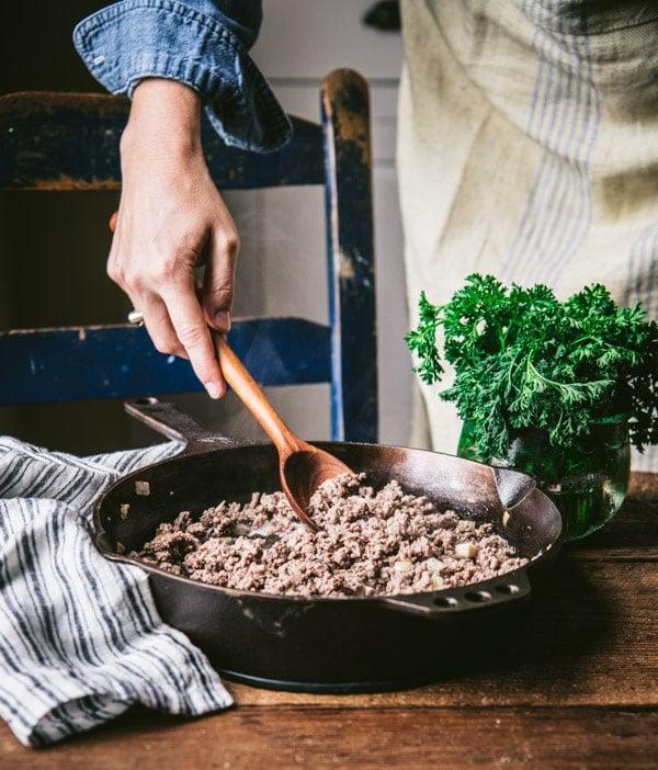 Stirring ground beef in a cast iron skillet