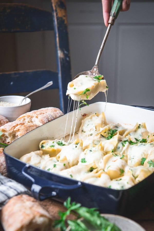 Spoon serving Chicken Alfredo Stuffed Shells