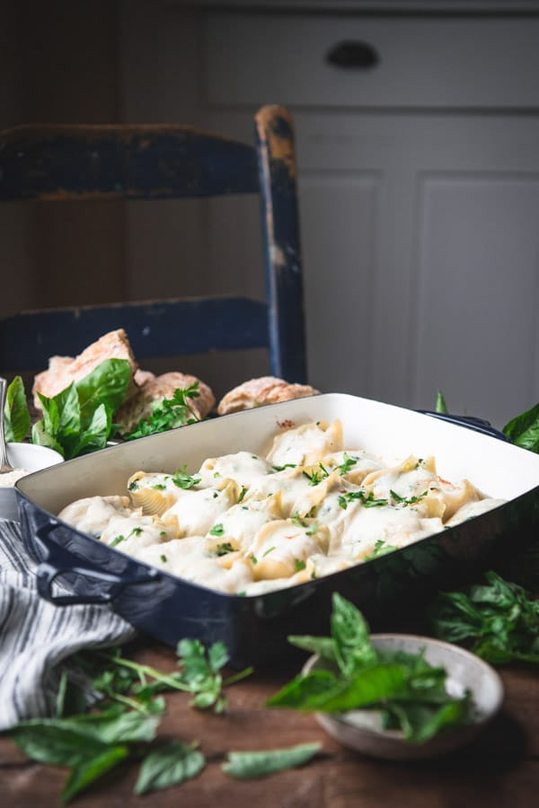 Side shot of a pan of chicken stuffed shells with spinach and ricotta on a farmhouse table