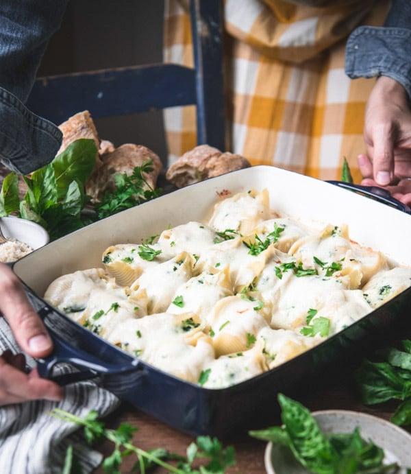 Hands serving a tray of chicken stuffed shells recipe