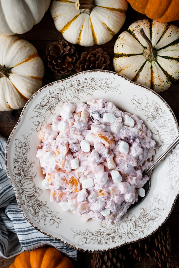 Close overhead image of cranberry fluff salad in a serving bowl on a wooden table.