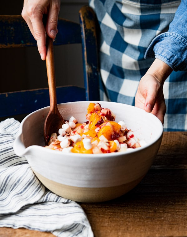 Stirring together a mixture of fruit and marshmallows in a white mixing bowl