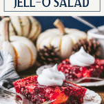 Two plates of cranberry jello salad on a Thanksgiving table with text title box at top