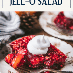 Cranberry jello salad on a plate with cool whip on top and text title box at top