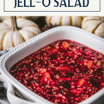 Close up shot of a white dish full of the best cranberry jello salad with text title box at top