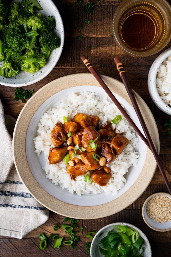Overhead shot of the best general tso chicken recipe served on a dinner table with broccoli and rice