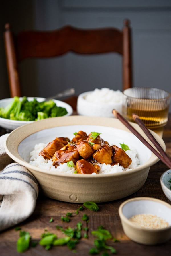 Baked healthy General Tso Chicken with a bowl of rice on a dinner table