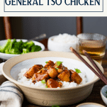Side shot of a bowl of the best general tso chicken recipe served over rice with text title box at top