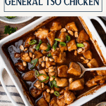 Baked general tso chicken in a white dish with text title box at top