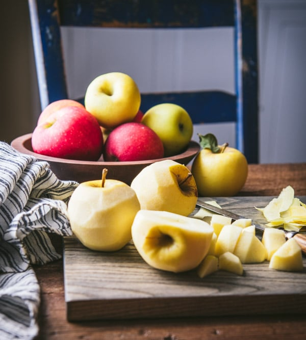 Fresh apples peeled and chopped on a cutting board
