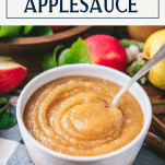 Spoon in a serving bowl of homemade applesauce with text title box at top