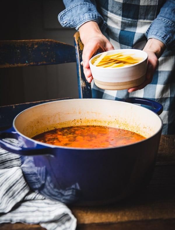 Adding lasagna noodles to a pot of soup