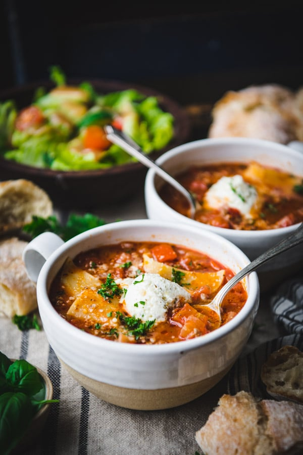 Side shot of two bowls of crockpot lasagna soup recipe on a dinner table