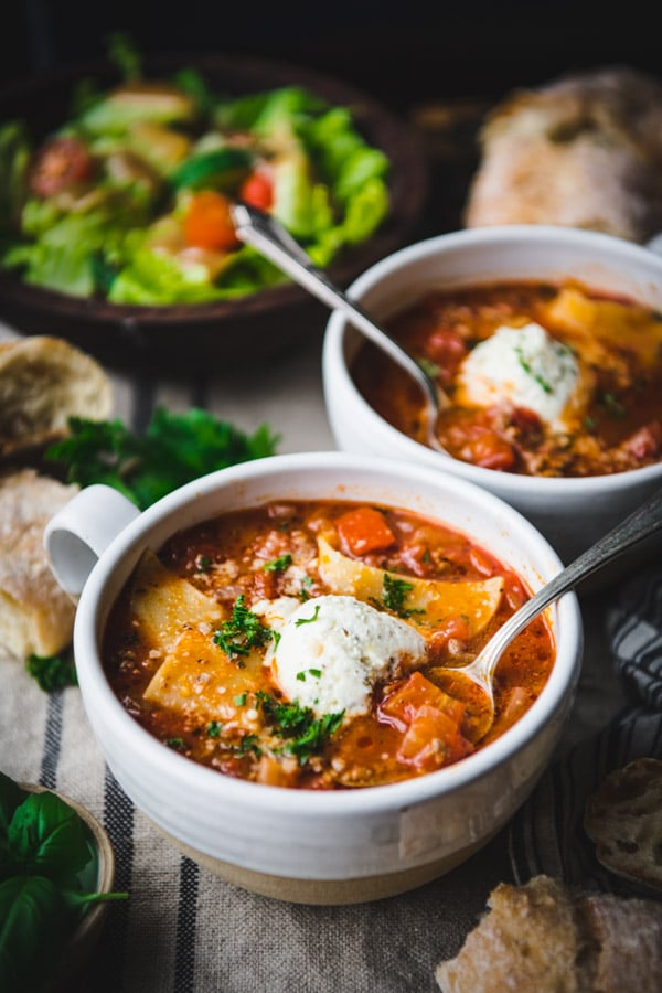 Side shot of easy lasagna soup in two white bowls on a table