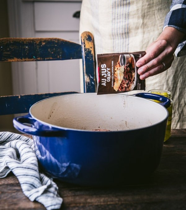 Sprinkling au jus gravy mix into a pot.