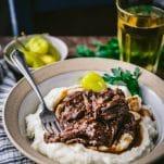 Close up side shot of easy Mississippi Pot Roast served over mashed potatoes on a dinner table.