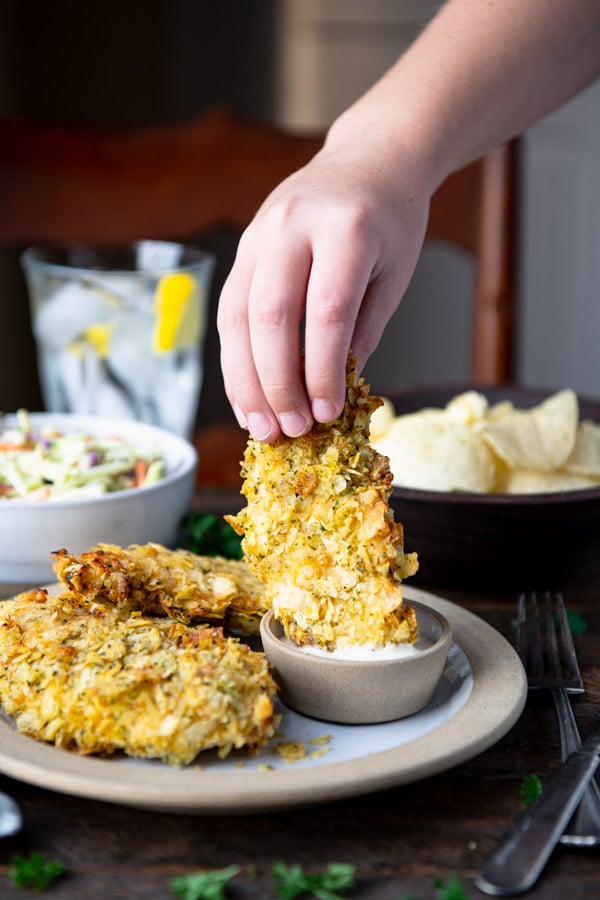 Kid's hand dipping potato chip chicken tenders in Ranch dip