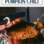 Pot of pumpkin chili with ladle and text title box at top
