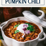 Close up side shot of a white bowl of pumpkin chili recipe with text title box at top