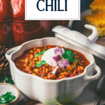 Side shot of turkey pumpkin chili on a table with text title overlay