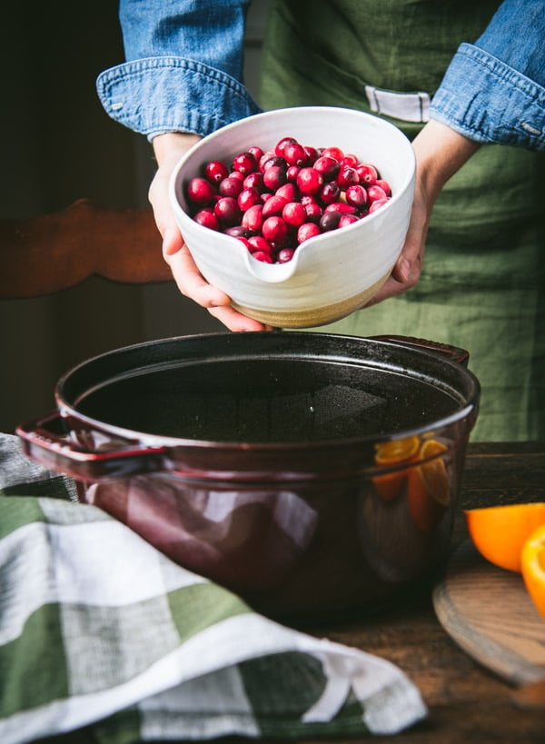 Adding fresh cranberries to a pot
