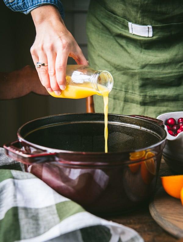Pouring orange juice into a pot