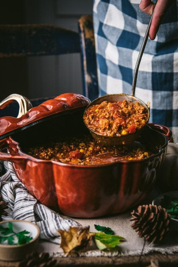 Ladle serving turkey pumpkin chili recipe from a pumpkin Dutch oven