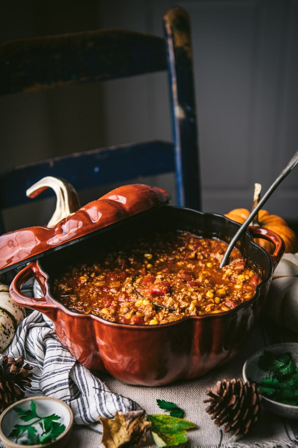 Side shot of a pot of pumpkin chili with a ladle for serving
